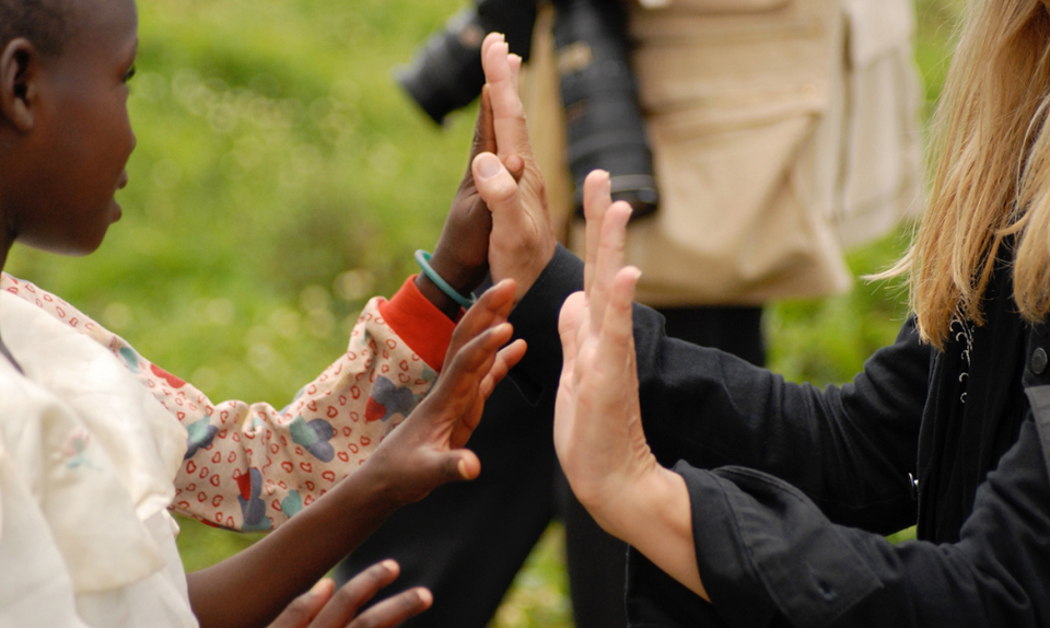 A white woman and african child reach out to grasp each other's hands