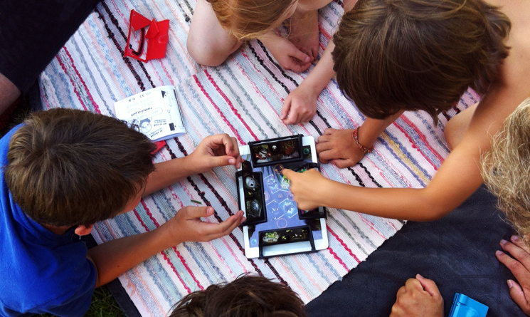 Children palying a game on a tablet. Credit: WikiLouise / Wikimedia